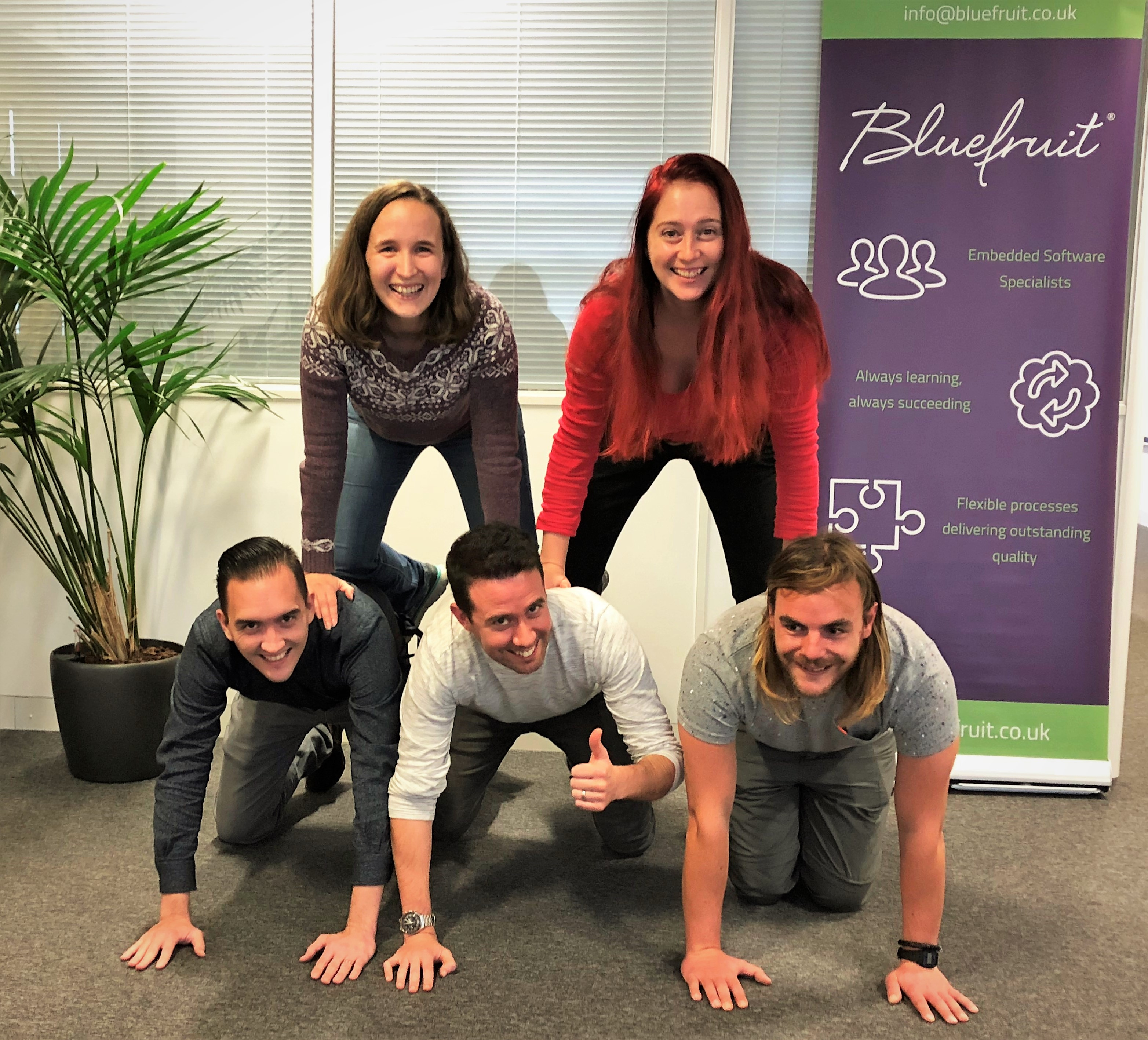 Several Bluefruit colleagues balanced in a human pyramid in the middle of the Bluefruit office.