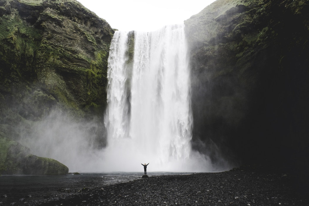 A person stands in front of a cascading waterfall.