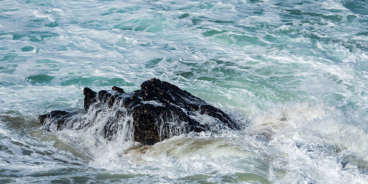 The sea foaming around a rock at Bedruthan, Cornwall.