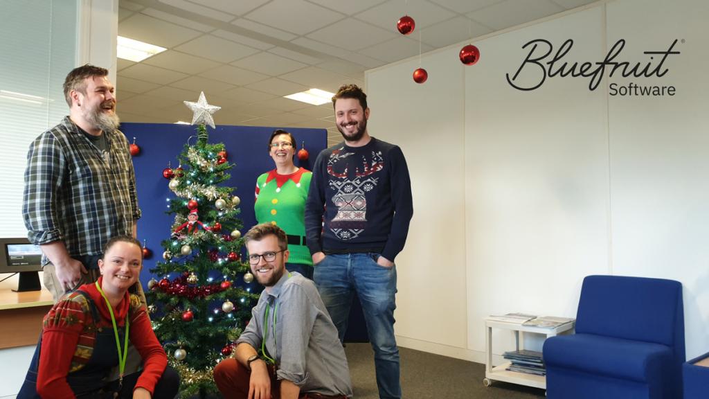 Bluefruit team beside a Christmas tree.